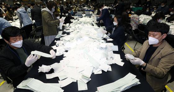 제21대 국회의원선거 투표가 종료된 15일 오후 서울 송파구 올림픽공원 KSPO돔에서 개표사무원들이 투표함을 열어 투표지 분류 작업을 하고 있다. 뉴스1