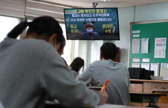 지난달 19일 오전 서울의 한 중학교에서 학생들이 코로나19 안전생활 수칙 관련 영상을 보고 있다. 뉴스1