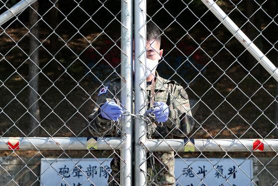 지난 10월 경기도 포천의 육군 부대에서 코로나19 확진자가 무더기로 발생하자 군 당국은 포천 지역 전 부대 장병에 대해 외출 통제령을 내렸다. 포천의 한 부대 관계자가 출입문에 자물쇠를 채우고 있다. [연합뉴스]