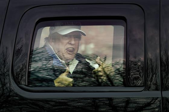 도널드 트럼프 미국 대통령이 22일(현지시간) G20 화상회의 도중 자리를 떠 버지니아에 있는 골프 클럽을 들렀다고 현지 언론들이 전했다. 사진은 트럼프 대통령이 골프 라운딩을 마치고 나오면서 자신의 지지자들을 향해 엄지를 들어 올리는 모습. [AFP=연합뉴스]