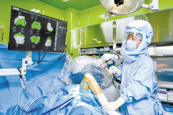 로봇 인공관절 수술은 3차원 CT와 로봇 팔 등 첨단 기술을 활용해 정확도가 높고 환자 회복이 빠르다. 강북힘찬병원 홍세정 원장이 로봇 인공관절 수술을 집도하고 있다. 김동하 객원기자