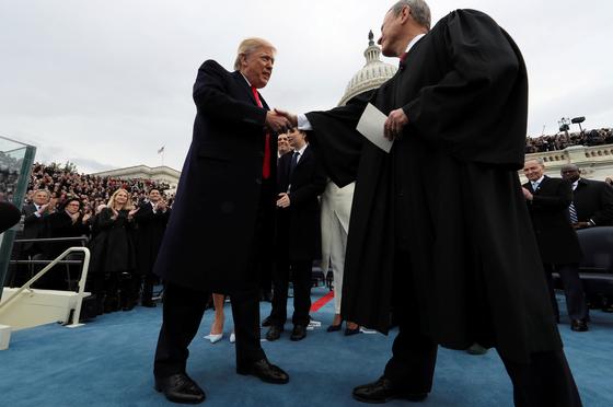 2017년 1월 20일 도널드 트럼프 미국 대통령이 제45대 미국 대통령 취임식에서 존 로버트 미국 연방대법원장 앞에서 선서를 한 직후 악수하고 있다. [로이터=연합뉴스]