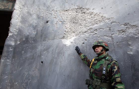 2010년 북한군의 포격 도발 당시 포탄을 맞은 연평도 자주포 진지 흔적을 한 해병대 장교가 설명하고 있다. [사진공동취재단]