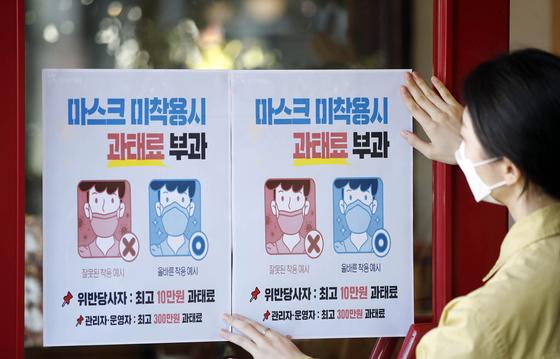 12일 오전 광주 북구의 한 커피숍에서 광주 북구보건소 감염병관리팀 직원들이 마스크 착용 의무화 시행으로 오는 13일부터 미착용 시 과태료를 부과한다는 안내문을 붙이고 있다. 연합뉴스