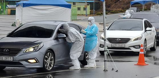 지난 19일 강원 철원군 공설운동장에 마련된 선별진료소에서 주민들이 드라이브스루 방식으로 검사를 받고 있다. 연합뉴스