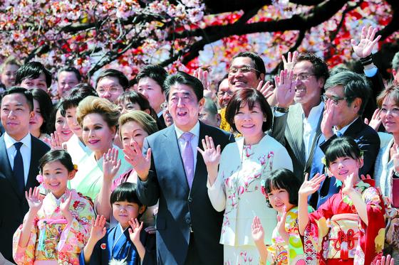 지난해 4월 신주쿠교엔 (新宿御苑)에서 개최된 '벚꽃을 보는 모임'에서 아베 신조 일본 총리와 아키에 여사가 연예인 등과 함께 기념촬영을 하고 있다. [지지통신]