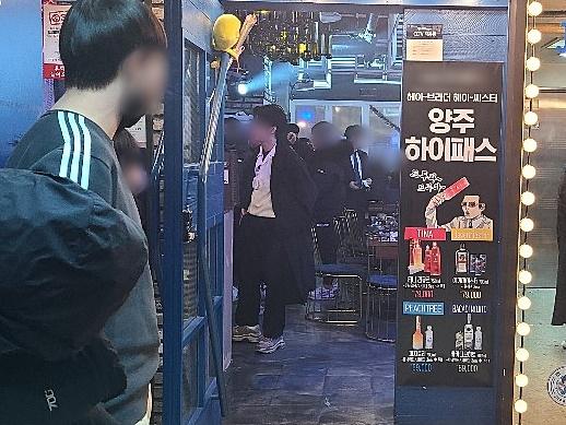 24일 0시 헌팅포차가 문을 닫으면서 계산을 위해 길게 늘어선 손님들. 채혜선 기자