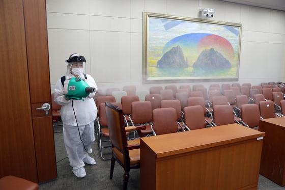 지난 9월 국회의사당 본관 상임위 회의실에서 방역당국 관계자가 방역작업을 하고 있다.  국회 제공=연합뉴스
