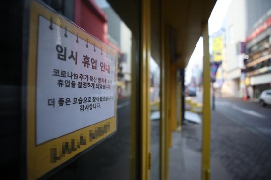 23일 서울 명동의 한 가게에 임시 휴업 안내문이 붙어 있다. 수도권의 '사회적 거리두기'는 24일부터 2단계로 격상된다. [연합뉴스]