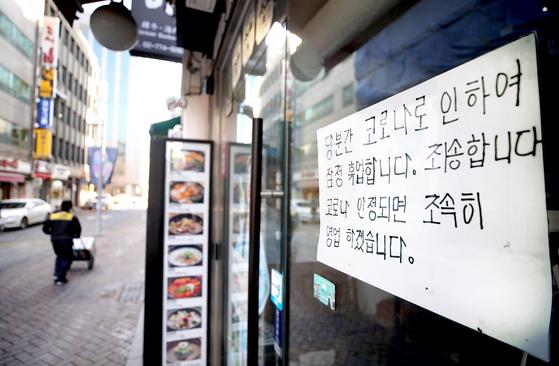 23일 서울 명동의 한 가게에 코로나19로 인한 임시휴업 안내문이 붙어 있다. [연합뉴스]