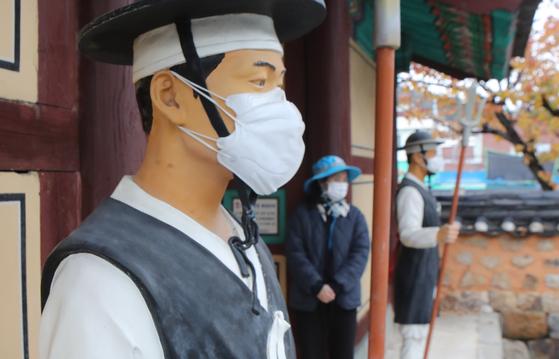 부산에서 코로나19 환자가 늘고 있다. 이를 반영하듯 22일 부산 동래구 옛 동래부동헌 입구 포졸 인형이 마스크를 2개나 쓴 채 근무하고 있다. 송봉근 기자