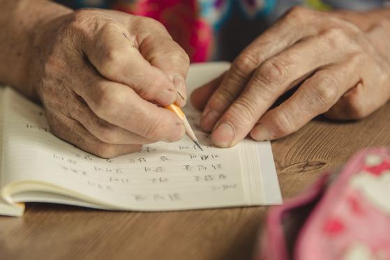 한글을 배워 시를 쓰는 칠곡할매들. 한 할머니가 연필로 손글씨를 쓰고 있다. [사진 칠곡군]