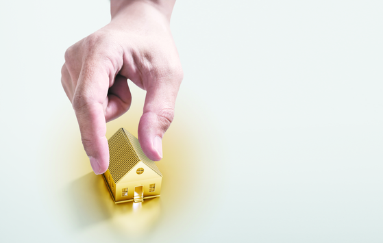 Hand picking golden house, real estate investment and buying house concept [Shutterstock]