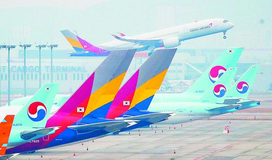 인천국제공항 주기장에 세워진 대한항공과 아시아나항공 여객기 뒤로 아시아나항공 여객기가 이륙하고 있다. 연합뉴스