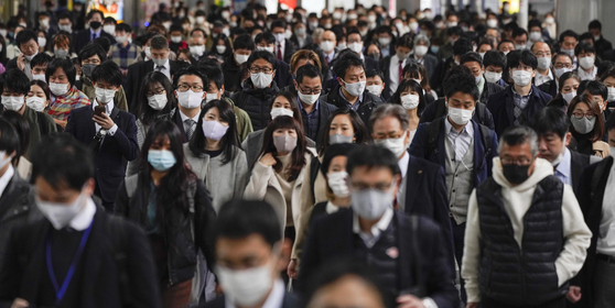 24일 마스크를 쓴 시민들이 일본 도쿄 시나가와역을 지나고 있다. [EPA=연합뉴스]