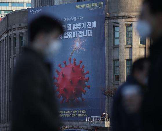 25일 오전 서울도서관 외벽에 천만 시민 긴급 멈춤 기간을 알리는 대형 현수막이 설치되고 있다. 연합뉴스