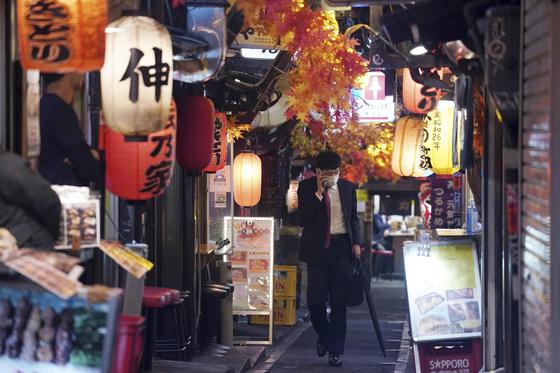 마스크를 쓴 한 시민이 25일 일본 도쿄 시내의 유흥가를 지나고 있다. [AP=연합뉴스]