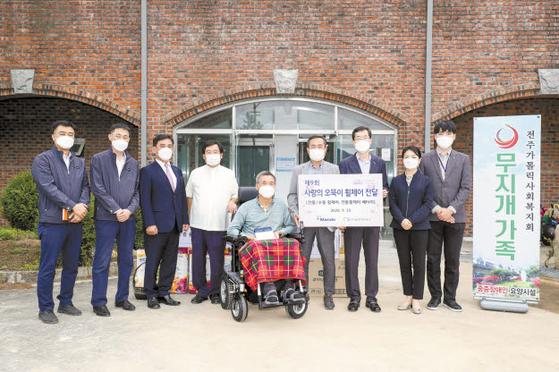 한국교통안전공단은 교통사고 중증후유장애인과 그 가족을 지원하는 다양한 사업을 20년째 진행하고 있다. 지난 9월 열린 '사랑의 오뚝이 휠체어 전달식'. [사진 한국교통안전공단]