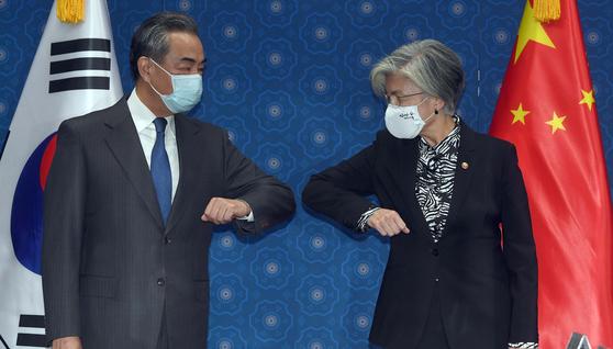 26일 외교부를 방문한 왕이 중국 외교부장이 강경화 외교부 장관과 회담 전 팔꿈치 인사를 나누고 있다. [사진공동취재단]