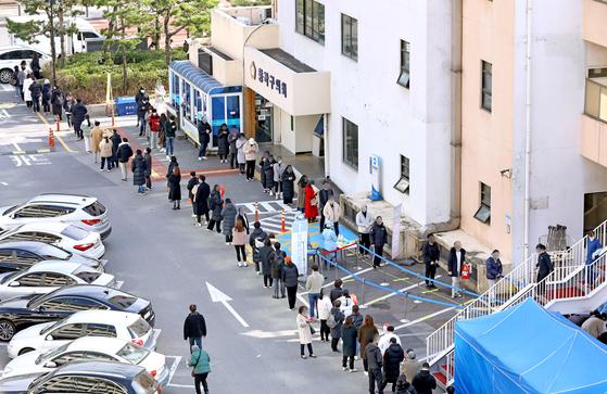 25일 오후 서울 동작구청 주차장에 마련된 선별진료소를 찾은 시민들이 코로나19 검사를 받기 위해 대기하고 있다. 뉴시스