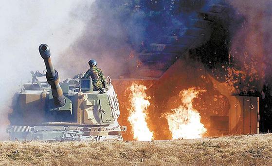 연평도 해병대 장병이 2010년 11월 23일 북한의 포격 도발로 진지가 불타고 있는 가운데 K-9 자주포에 올라 대응사격을 준비하고 있다. 당시 임준영 상병은 철모가 불타는 것도 아랑곳하지 않고 K-9에서 임무를 수행했다. [사진 국방부]