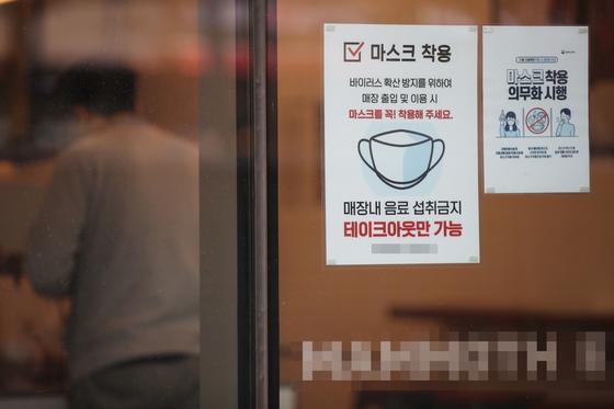 """한 카페 앞에 """"테이크 아웃만 가능""""이라고 적힌 안내문이 붙어 있다. 연합뉴스"""