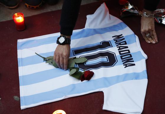 이탈리아 나폴리의 팬이 마라도나 유니폼 위에 헌화하며 추모하고 있다. 로이터=연합뉴스