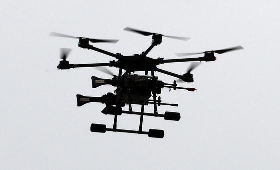 지난 18일 열린 2020 대한민국 방위산업전(Defense & Security Expo Korea 2020)에서 소총으로 무장한 육군 드론봇이 하늘을 날고 있다. [뉴스1]