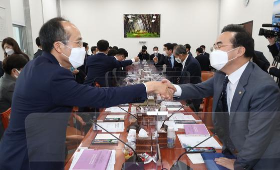 16일 예결위 소위 회의에 앞서 더불어민주당 박홍근 간사(오른쪽)와 국민의힘 추경호 간사가 악수를 나누고 있다. 오종택 기자