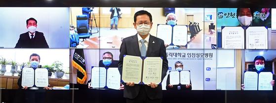 박남춘 인천광역시장이 접견실에서 열린 '1회용품 없는 장례문화 조성을 위한 비대면 업무협약식'에서 서명한 협약서를 들고 기념촬영을 하고 있다.