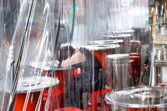 국내 신종 코로나바이러스 감염증(코로나19) 일일 신규 확진자가 이틀 연속 500명을 넘으며 3차 대유행이 현실화되는 가운데 26일 오후 서울 중구 남대문시장의 한 음식점에서 직원이 휴식을 취하고 있다. 뉴스1