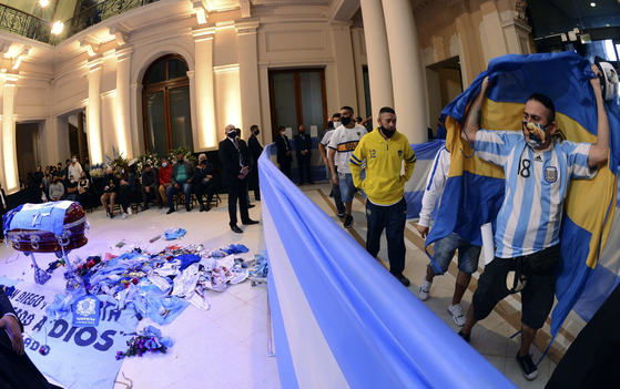 Argentine people continue to celebrate at the coffin of Diego Maradona in the presidential palace in Argentina on the 26th.  AP=Yonhap News