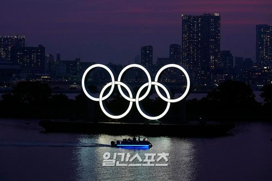 FILE - In this June 3, 2020, photo, the Olympic rings float in the water at sunset in the Odaiba section in Tokyo. The postponed Tokyo Olympics have again reached the one-year-to-go mark. But the celebration is small this time with more questions than answers about how the Olympics can happen in the middle of a pandemic. That was before COVID-19 postponed the Olympics and pushed back the opening to July 23, 2021. (AP Photo/Eugene Hoshiko, File)