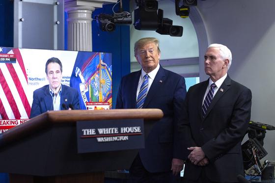 트럼프 대통령(가운데)과 마이크 펜스 부통령이 지난 4월 백악관 기자회견장에서 앤드루 쿠오모 뉴욕주지사의 코로나19 관련 발표 내용을 듣고 있다. 이후에도 트럼프 대통령과 쿠오모 주지사는 코로나19 대응 방식을 놓고 자주 날카롭게 부딪쳤다. [EPA=연합뉴스]
