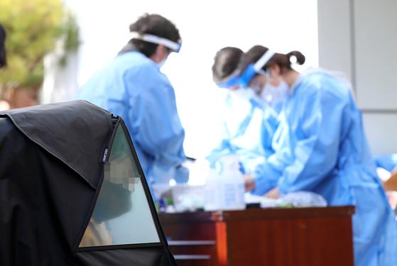 28일 오후 대전시 유성구 한 초등학교에 마련된 신종 코로나바이러스 감염증(코로나19) 임시 선별진료소에서 유모차에 탄 어린이가 검사 순서를 기다리고 있다. 연합뉴스
