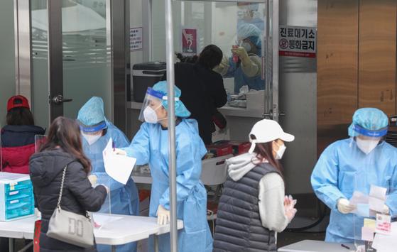 26일 오전 서울 강서구보건소 내 선별진료소에서 시민들이 코로나19 검사를 받기 위해 줄을 서 있다. 뉴스1