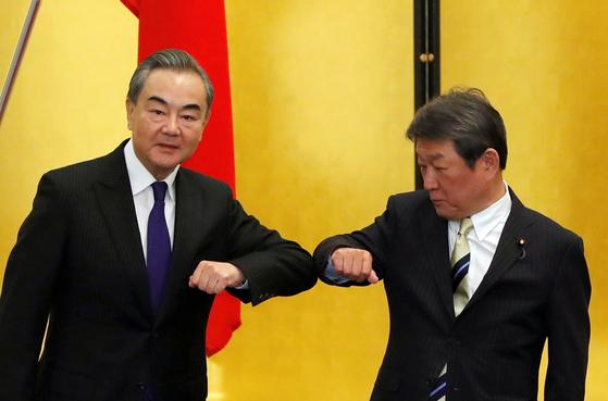 24일 회담한 중국 왕이 외교부장(왼쪽)과 모테기 도시미쓰 일본 외무상이 팔꿈치를 부딪하며 인사를 하고 있다. [로이터=연합뉴스]