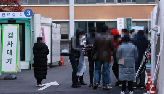 30일 오전 서울 중구 국립중앙의료원 신종 코로나바이러스(코로나19) 선별진료소에서 검체 채취를 마친 시민들이 병원 관계자의 안내를 받고 있다. 연합뉴스