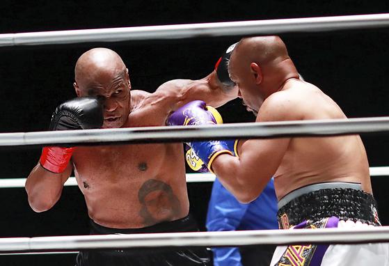 마이크 타이슨(왼쪽)이 28일 열린 로이 존스 와의 복싱경기 에서 펀치를 날리고 있다. [AP=연합뉴스]