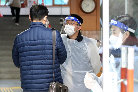 지난 21일 오전 대구 달서구 경북기계공업고등학교에서 응시자들이 고사장 입실에 앞서 손 소독과 발열체크를 받고 있다. 뉴스1