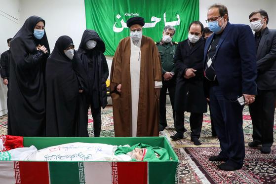 이란의 사법부 수장인 아야톨라 에브라힘 라이시(가운데)가 28일 피살당한 이란의 핵 과학자 모센 파크리자데의 시신 앞에서 조문하고 있다. [AP=연합뉴스]