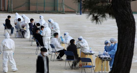 30일 오후 광주 광산구의 한 중학교에 설치된 선별진료소에서 학생들이 신종 코로나바이러스 감염증(코로나19) 검사를 받고 있다. 연합뉴스