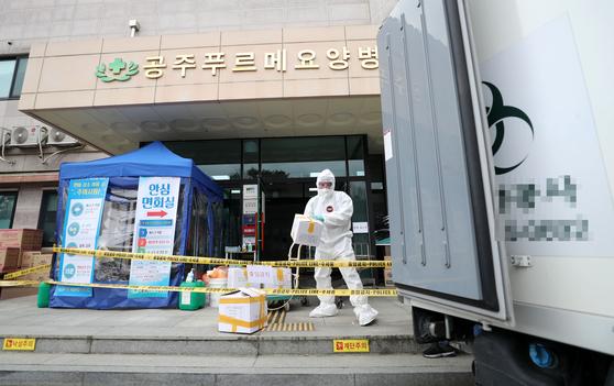지난달 27일 충남 공주시 푸르메요양병원 입구에서 폐기물 처리업체 관계자가 의료용 폐기물을 옮기고 있다. 푸르메요양병원 관련 코로나19 확진자는 모두 45명으로 늘었다. 연합뉴스