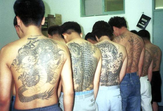 지난 2003년 6월 3일 현역 복무를 피하기 위해 몸에 문신을 새긴 20대 대학생과 회사원 등 36명이 전남지방경찰청 기동수사대에 붙잡혀 조사를 받고 있다. '병역판정 신체검사 규칙' 개정안에 따라 앞으로는 온몸에 문신을 해도 현역병으로 입대할 수 있게 된다. [뉴시스]
