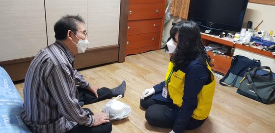 """지난달 19일 관악돌봄SOS센터 매니저가 거동이 불편한 김성영(71)씨를 찾아 식사를 건네고 있다. 홀로 사는 김씨는 코로나19로 복지관 식당이 문을 닫자 반찬을 사러 다니다 넘어져 크게 다쳤다. 파킨슨병을 앓고 있는 그는 """"다리에 힘이 없어 일어서기가 힘들다""""고 말했다. 김현예 기자"""