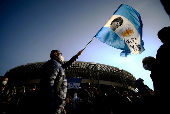 디에고 마라도나를 추모하는 내용의 아르헨티나 국기를 흔드는 축구팬. [AFP=연합뉴스]