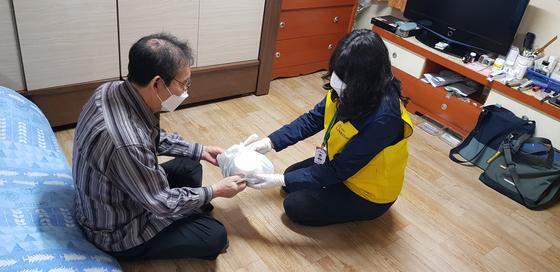지난달 19일 관악돌봄SOS센터 매니저가 거동이 불편한 김성영(71)씨를 찾아 식사를 건네고 있다. 김씨는 코로나로 복지관 식당이 문을 닫자 반찬을 사러 다니다 넘어져 크게 다쳤다. 김현예 기자
