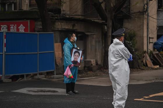 지난 3월 31일 우한시의 볜단산(扁担山) 공동묘지 인근에서 한 시민이 가족의 영정을 들고 서있다. AFP 통신이 선정한 2020년 올해의 사진이다. [AFP=연합뉴스]