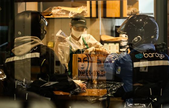 음료 배달을 맡은 라이더가 27일 오후 스타벅스 딜리버리 매장에서 음료 포장을 기다리고 있다. [연합뉴스]
