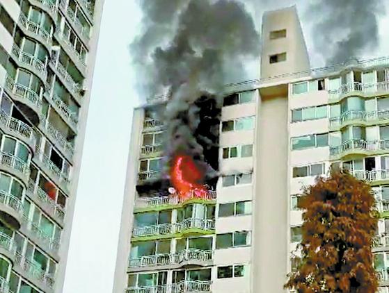 1일 경기도 군포시 산본동의 15층짜리 아파트 12층에서 화재가 발생해 4명이 숨지는 사고가 발생 했다. 경찰과 소방 당국은 아파트 리모델링 공사 중 불이 났다는 목격자 진술을 토대로 자세한 화재 경위를 조사하고 있다. 사진은 화재가 발생한 아파트에서 불길이 치솟고 있는 모습. [연합뉴스]